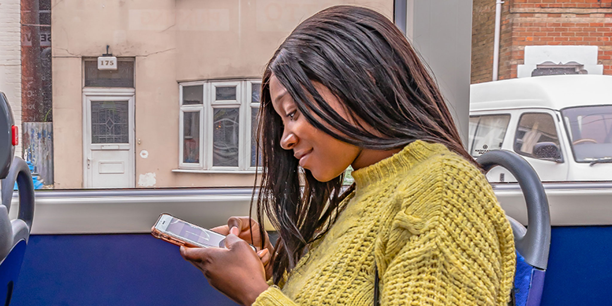 Photo of a lady using on-board bus Wi-Fi on her mobile phone