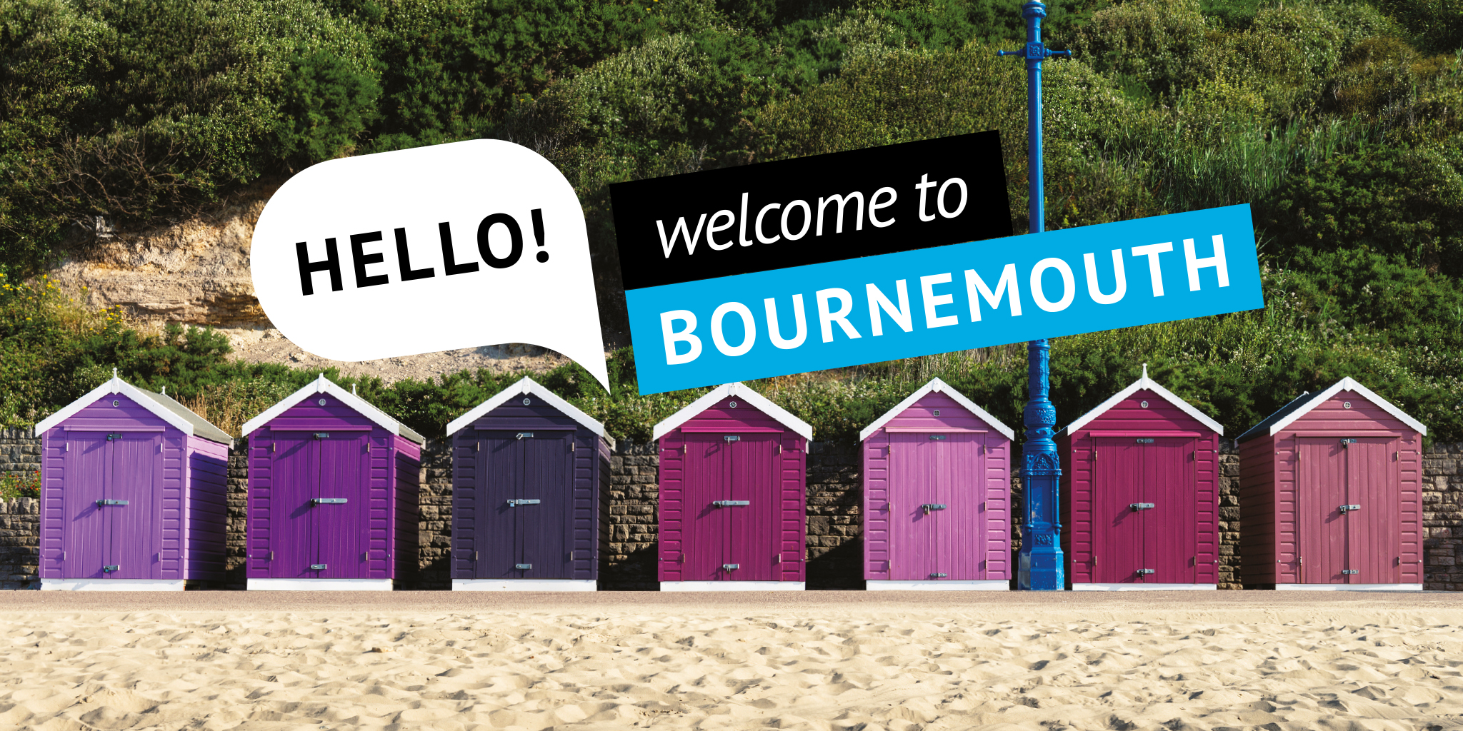 Photo of some pink and purple beach huts with the words 'Hello! Welcome to Bournemouth' overlaid