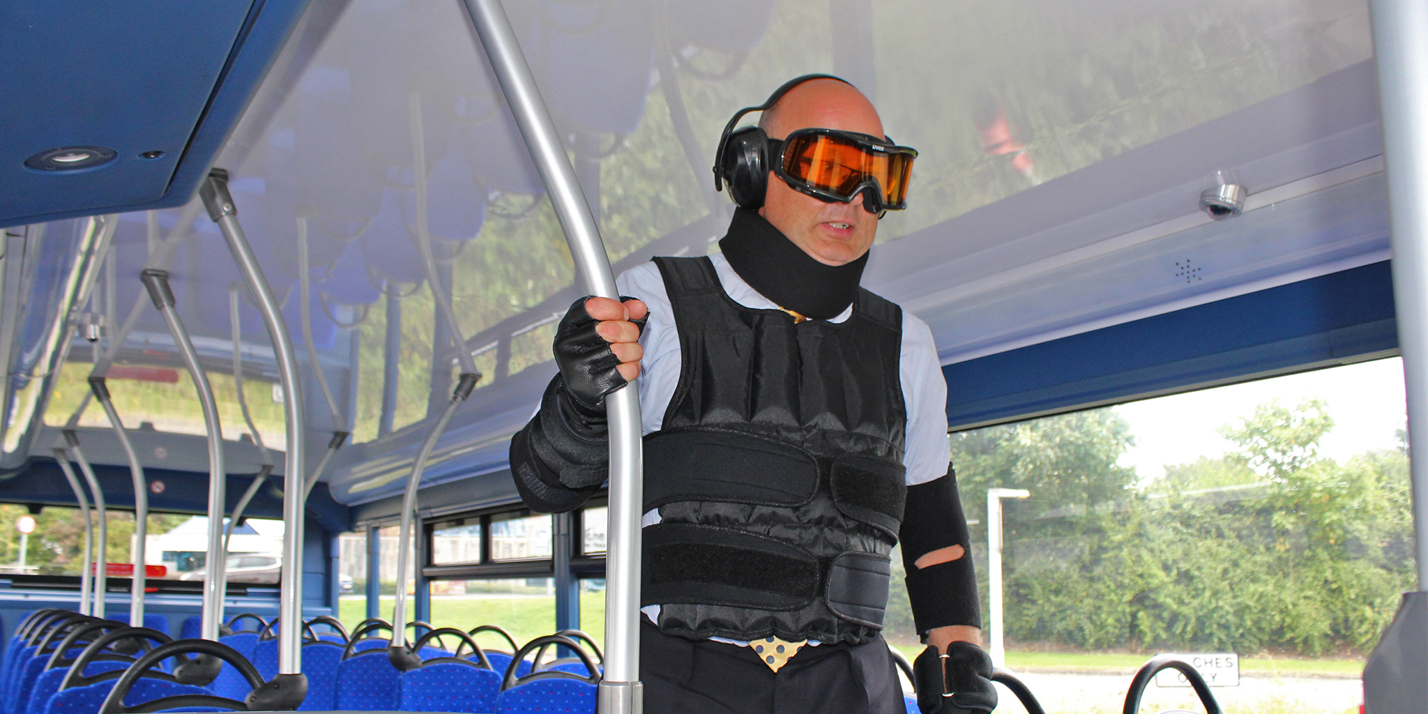A man wearing ear defenders and protective eye and body wear