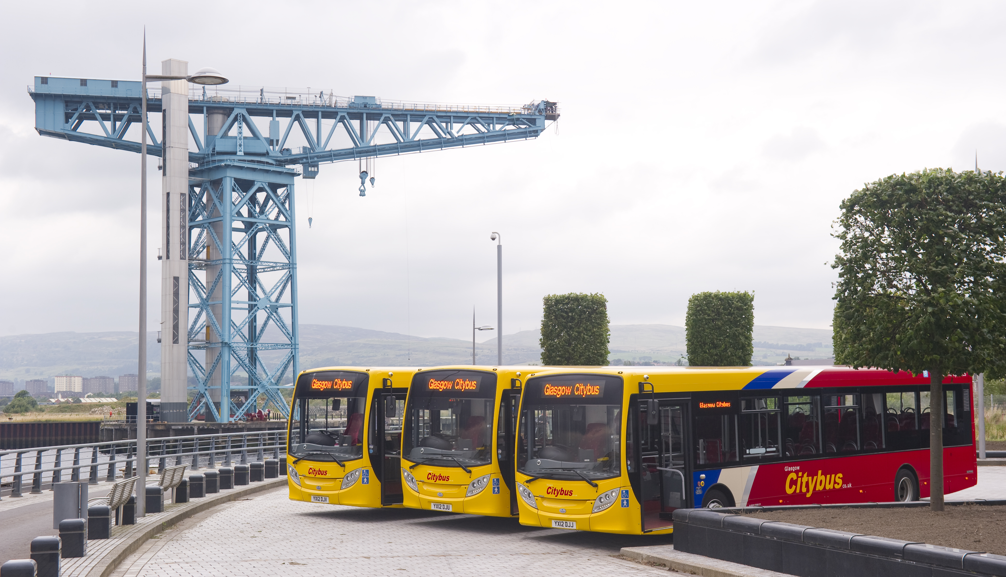 three yellow and red buses in front of the blue titan crane