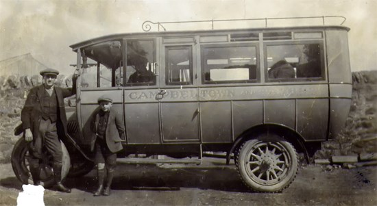 man and boy in black and white photo next to wagon