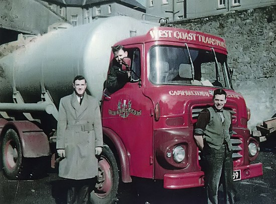 two young men standing in front of lorry