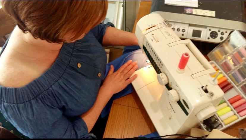 woman bent over sewing machine