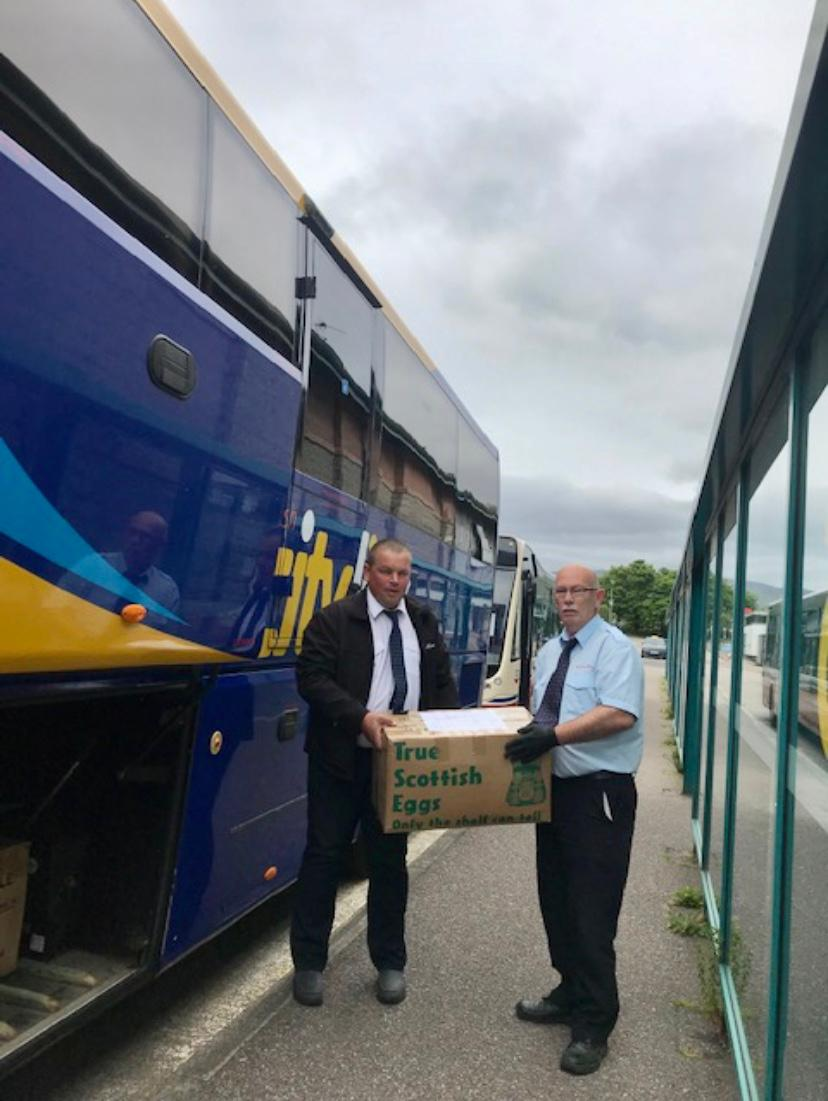 two men standing in front of blue coach holding boxes