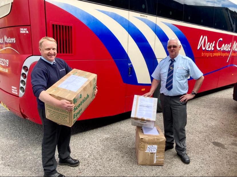 two men standing in front of red coach holding boxes