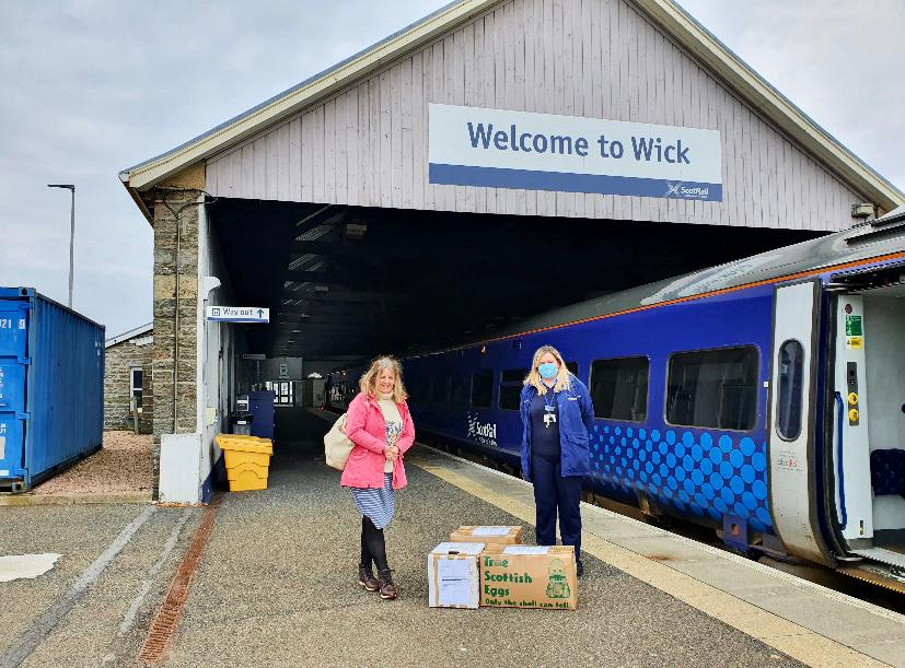 two women stand with cardboard boxes in front of Wick train station