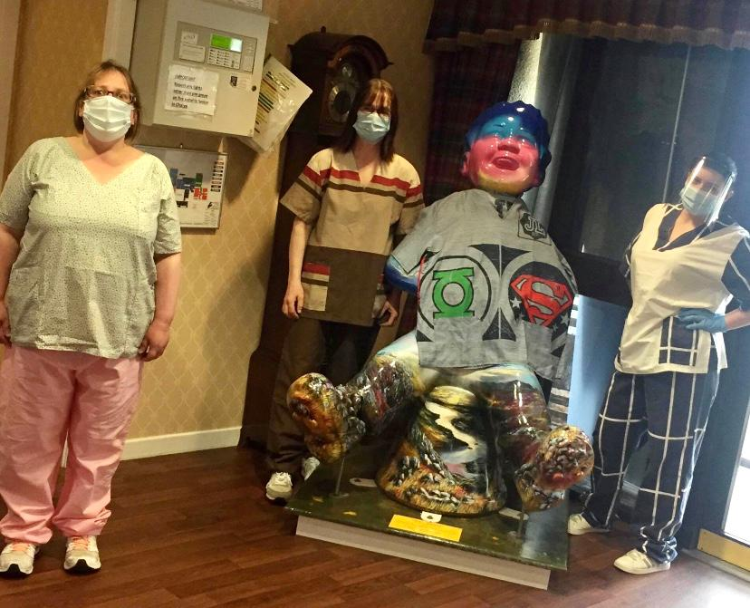 care home workers wearing new hand-made scrubs posing next to large Oor Wullie statue