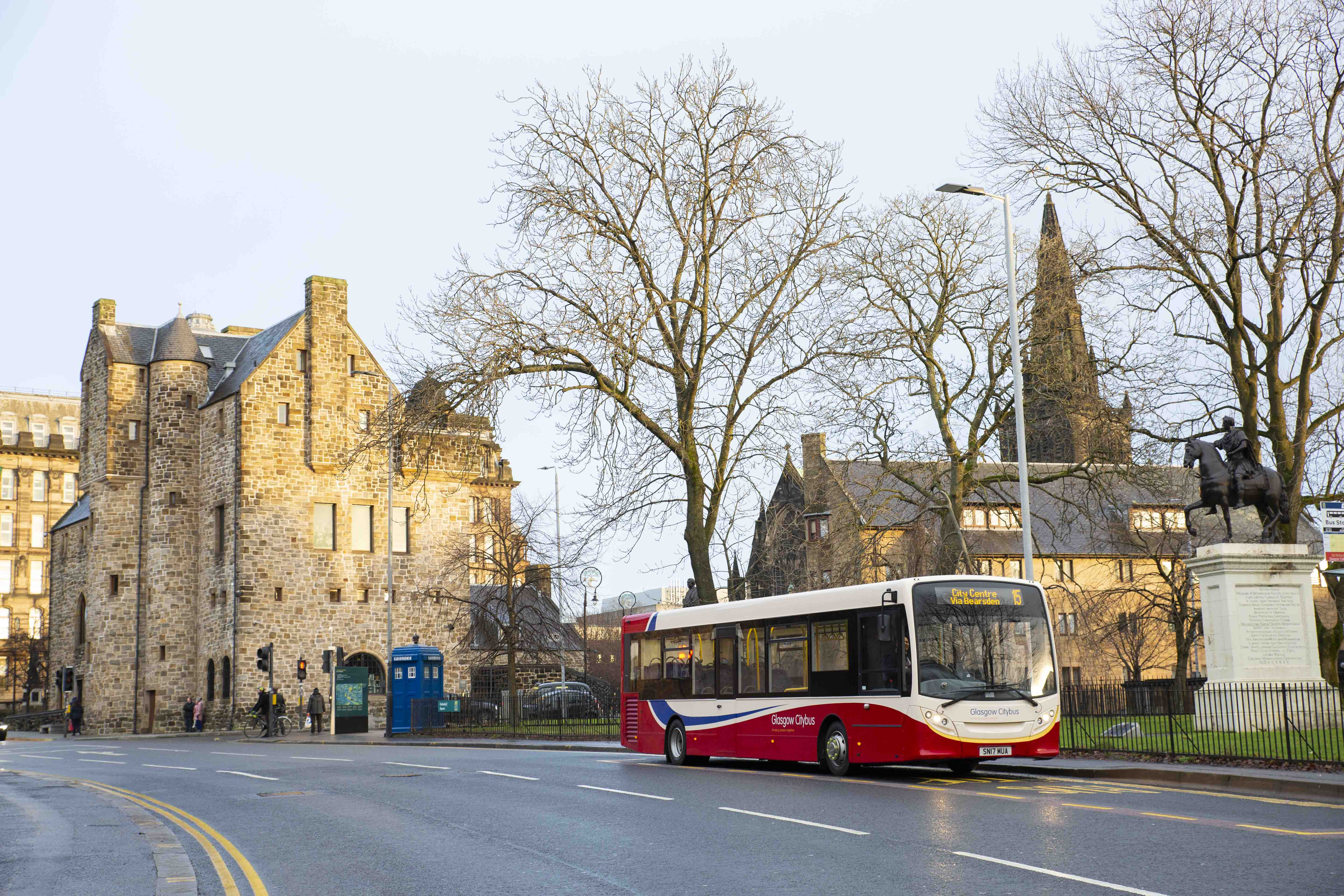 red and cream bus outside glasgow cathedral
