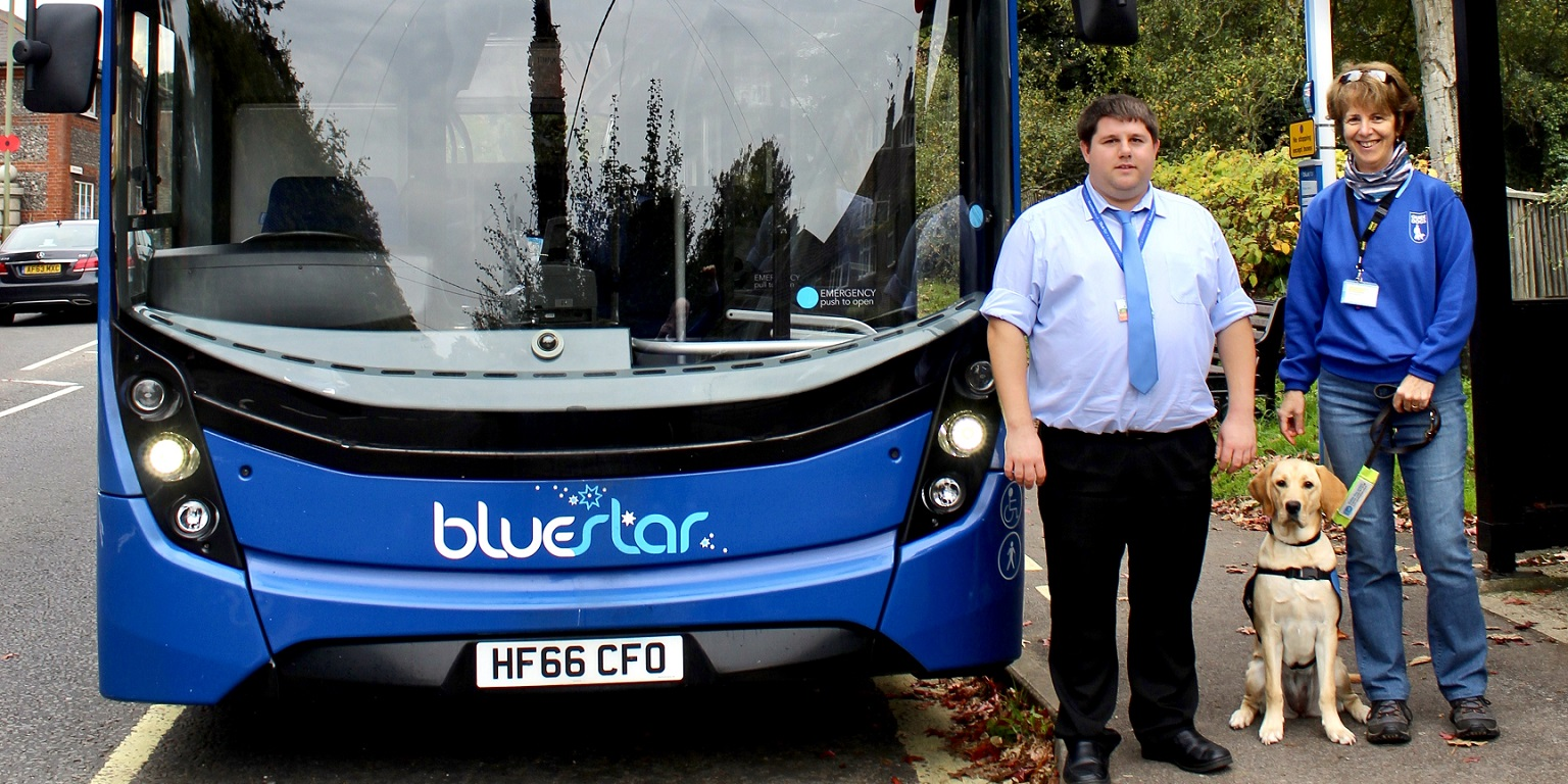 Bluestar's George Miller with trainer Jane Tabor and Guide Dog Poppy stand next to the front of a Bluestar Bus
