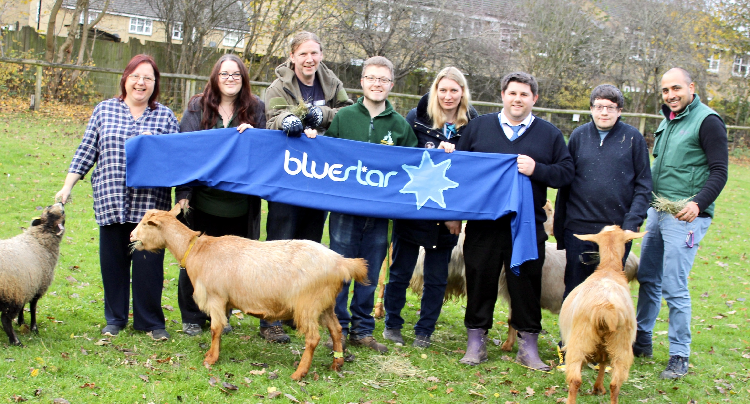 Volunteers from Southampton City Farm and Bluestar's George Miller pose surrounded by farm animals and a banner with the Bluestar logo