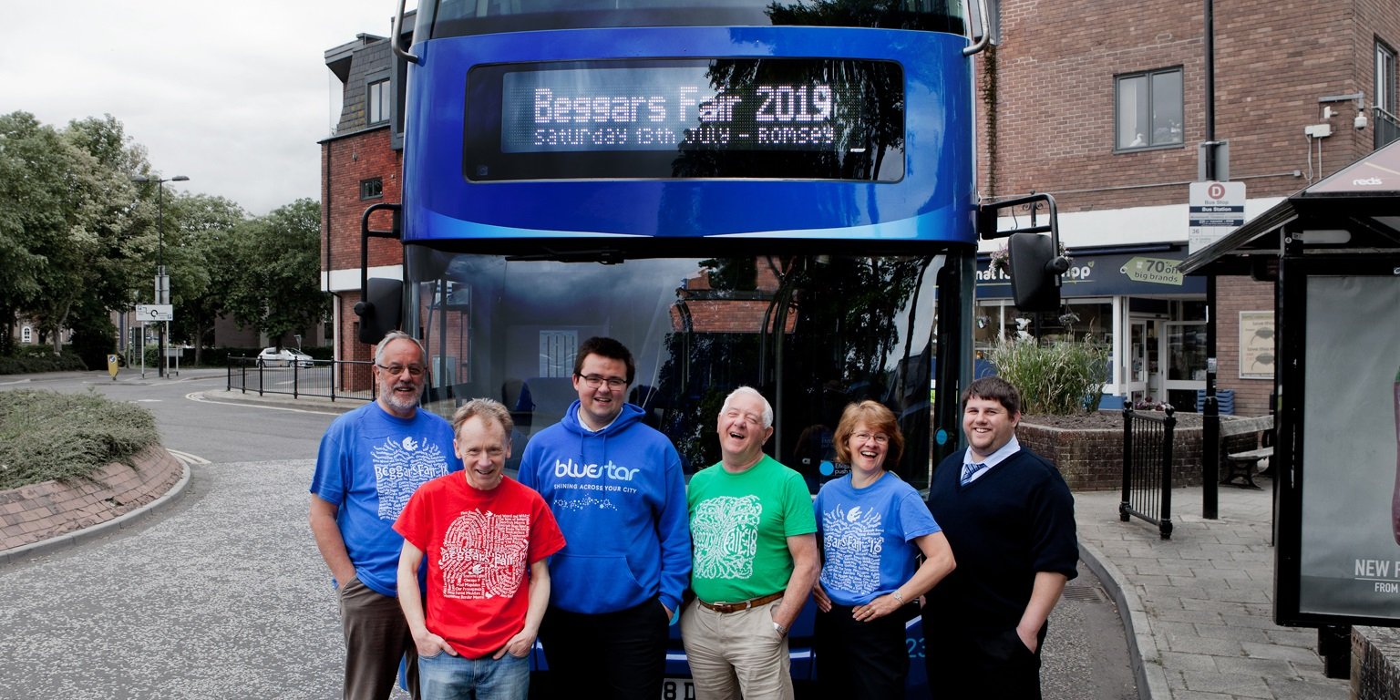 Representatives from the Beggars Fair and Bluestar pose laughing in front of a bus