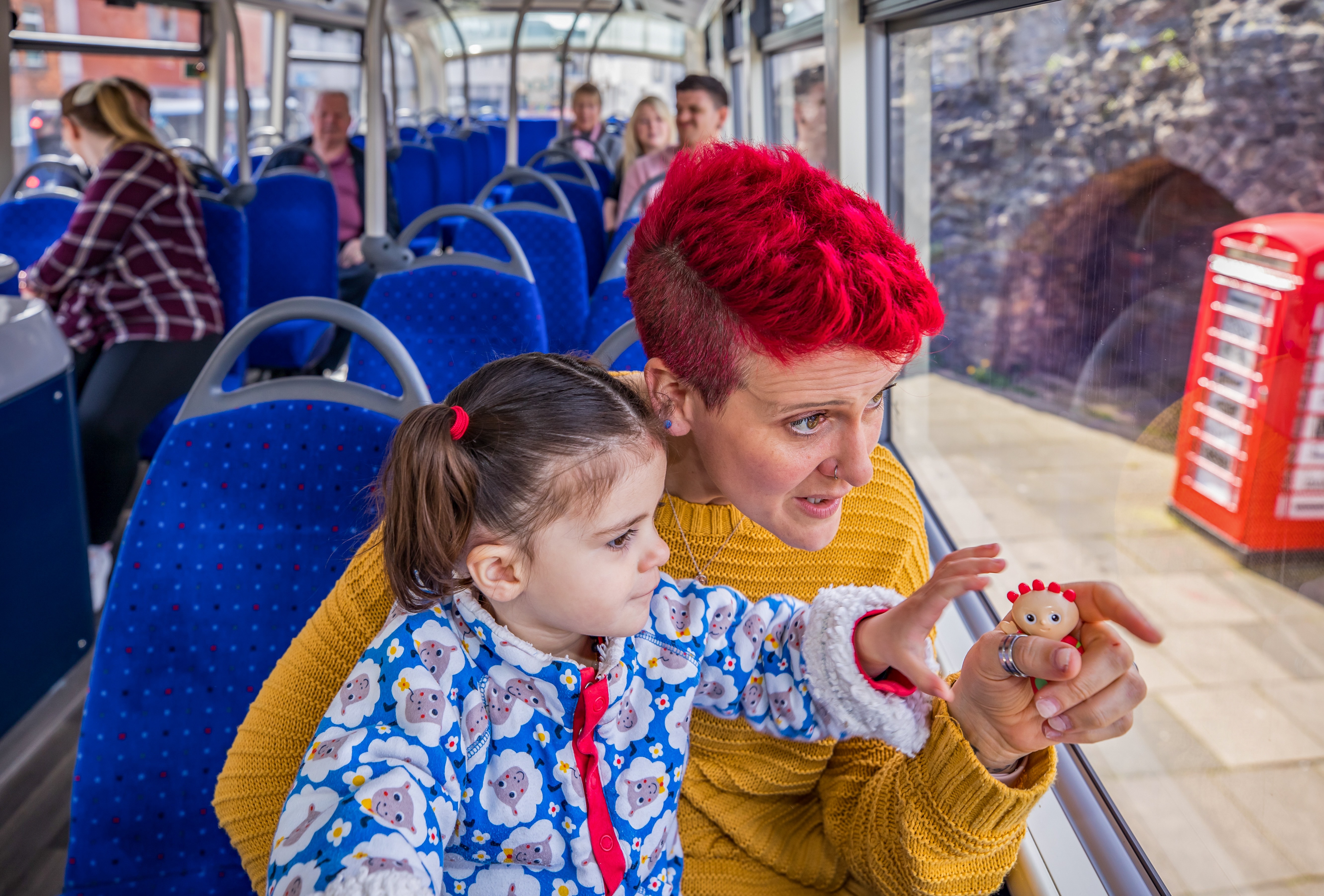 Mum and child on bus pointing out the window