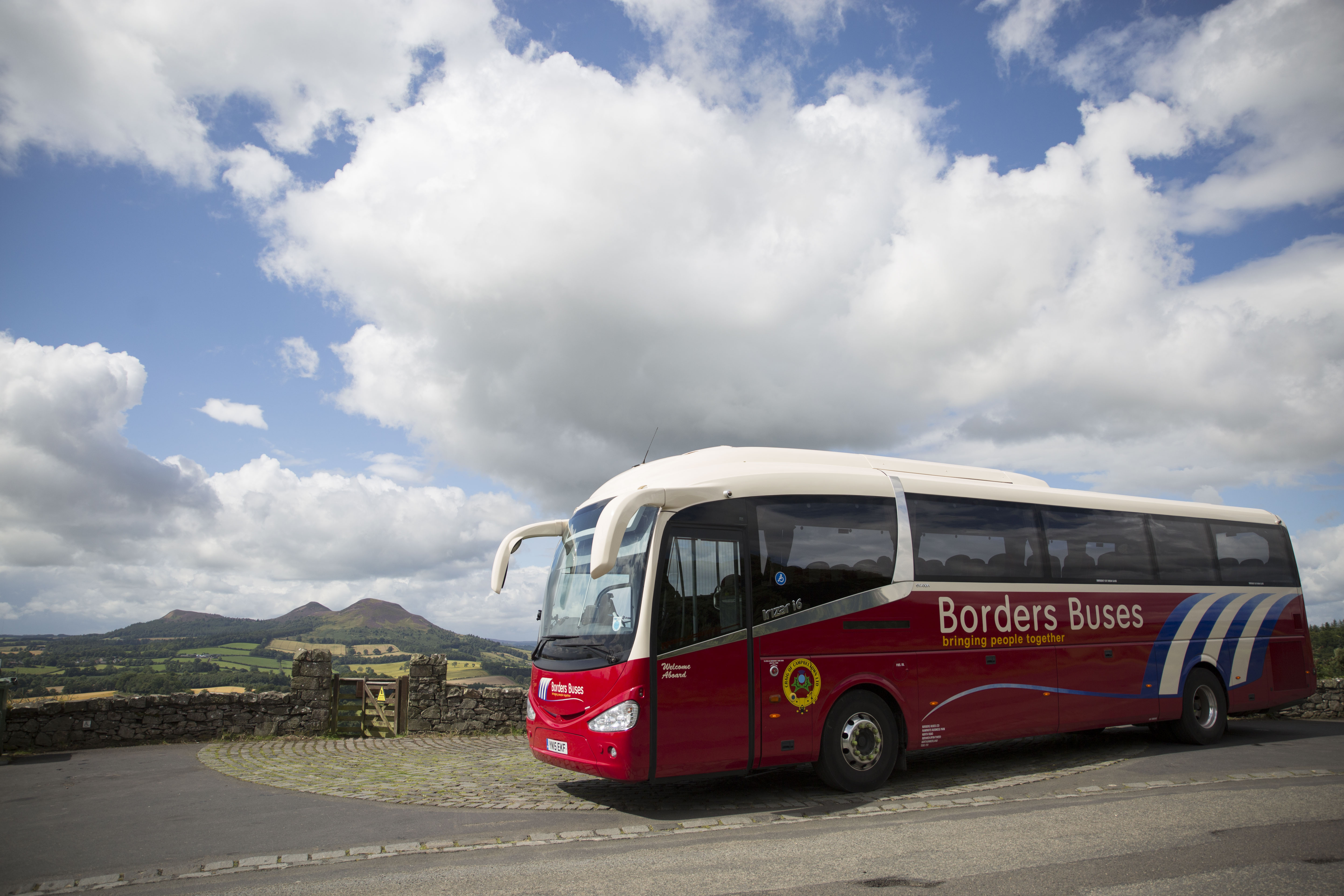 Borders buses red coach with Scotts view in the background