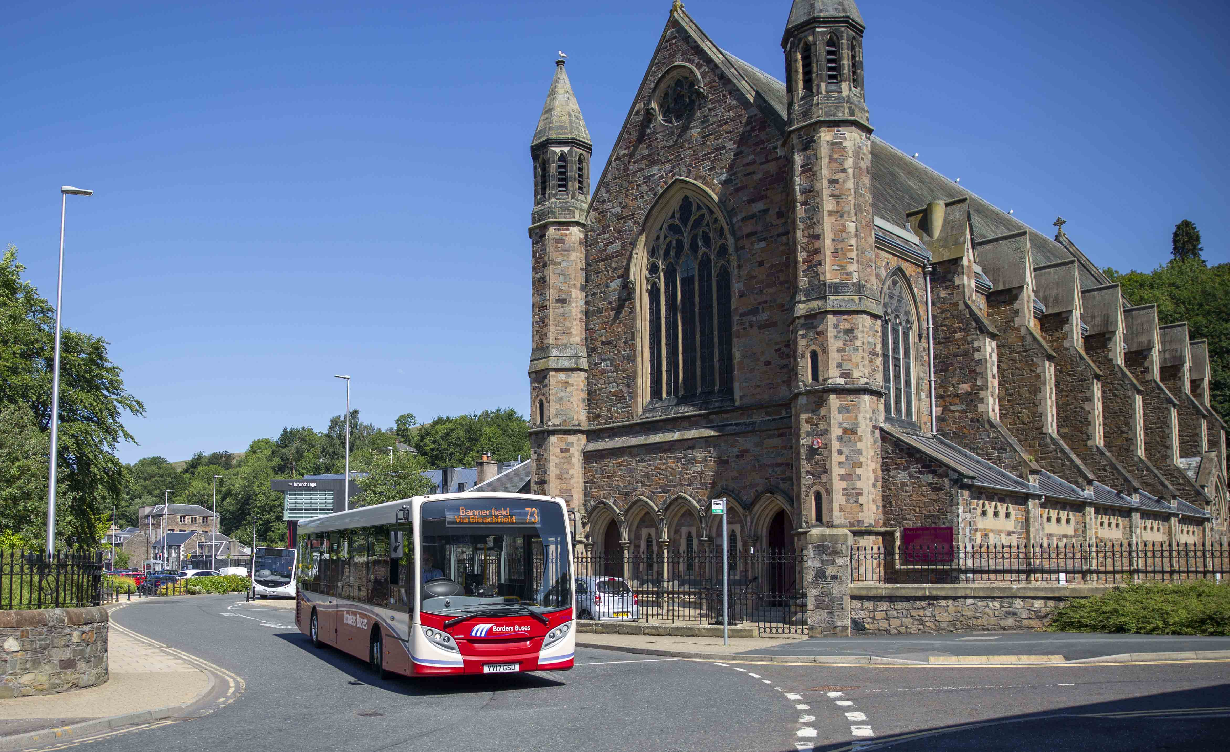 red bus in front of old church in Galashiels