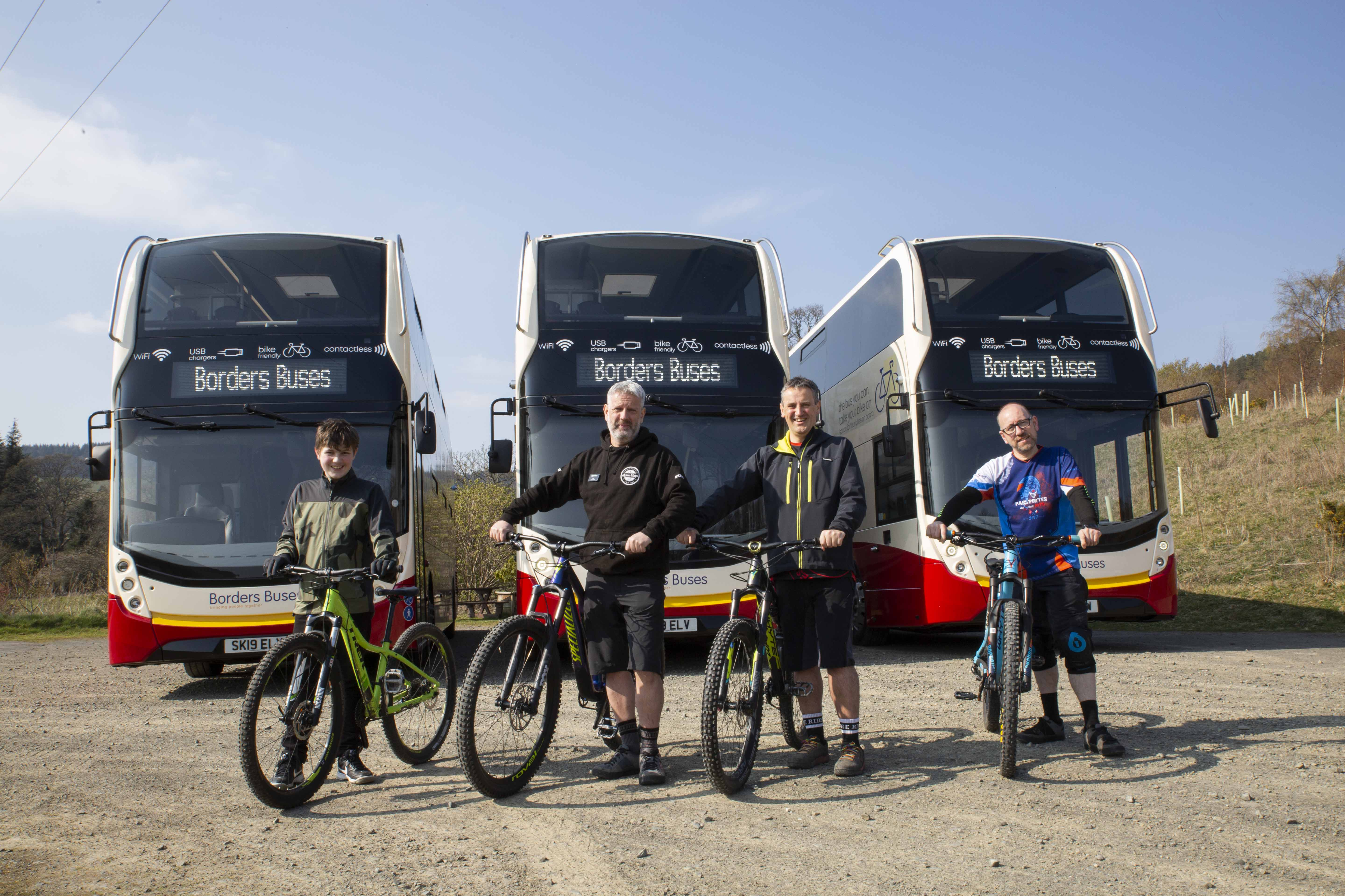 Four cyclists holding their bikes at Glentress forrest with three double decker buses in the background