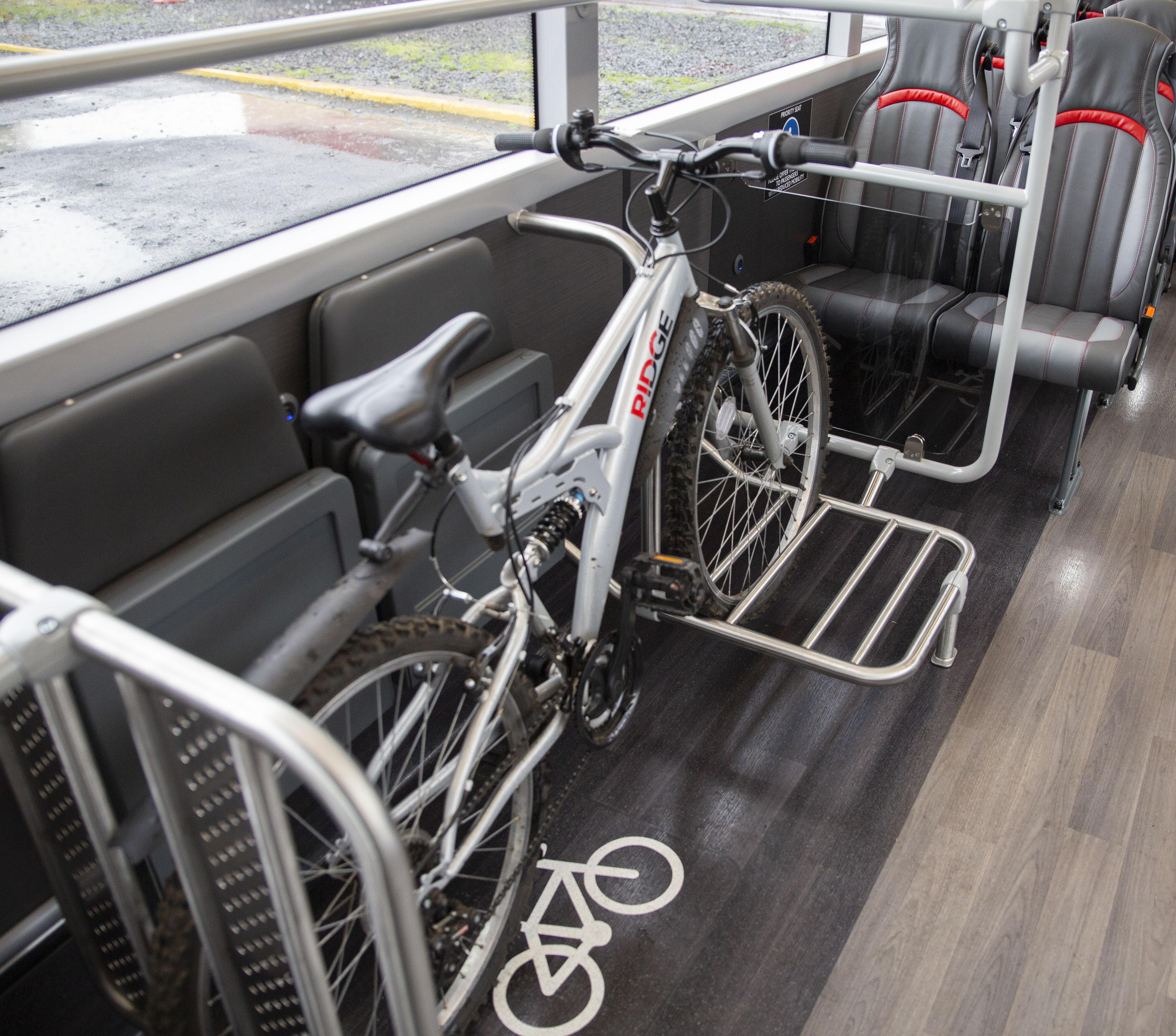 silver bike on bike rack on bus