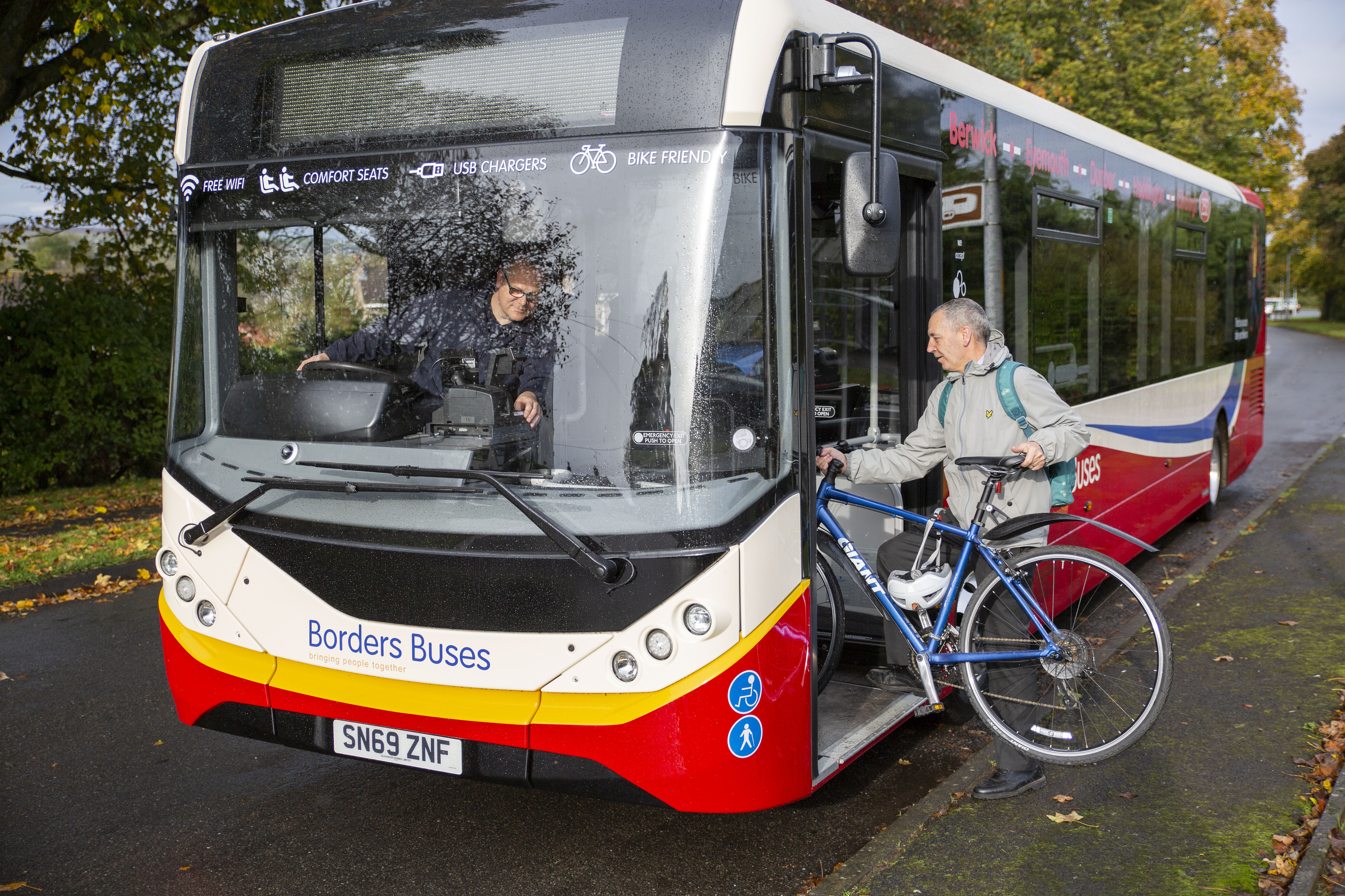 man gets on bus with bike