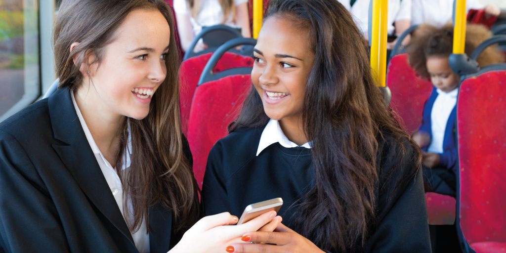 Image of two young people on a bus holding their phone