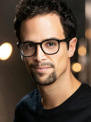 2020 Headshot with glasses · By: Adam Hills