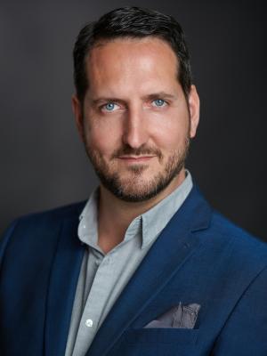 2021 Portrait: blue jacket, grey shirt, open collar. · By: David Myers