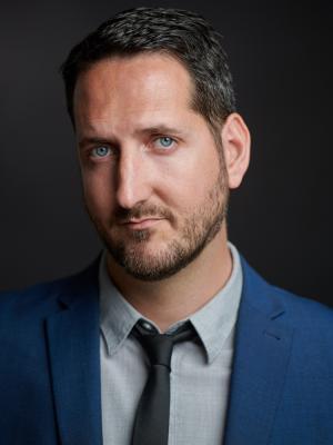 2021 Portrait: slight profile, blue jacket, grey shirt, black tie · By: David Myers