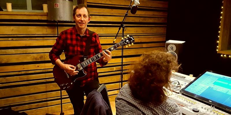 Rick Alancroft playing guitar in a recording studio