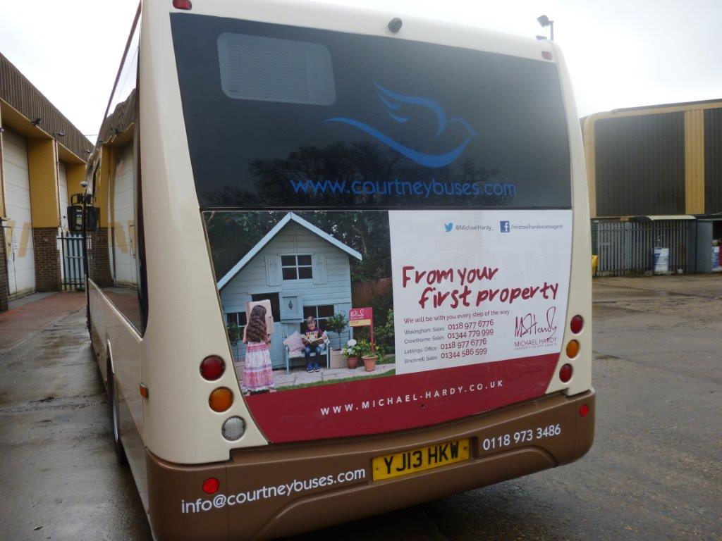 A Courtney Bus with an advertisement on the back