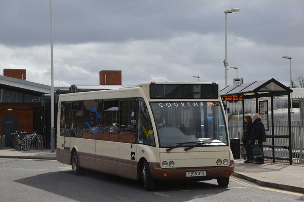 A Courtney bus collecting passengers at a stop