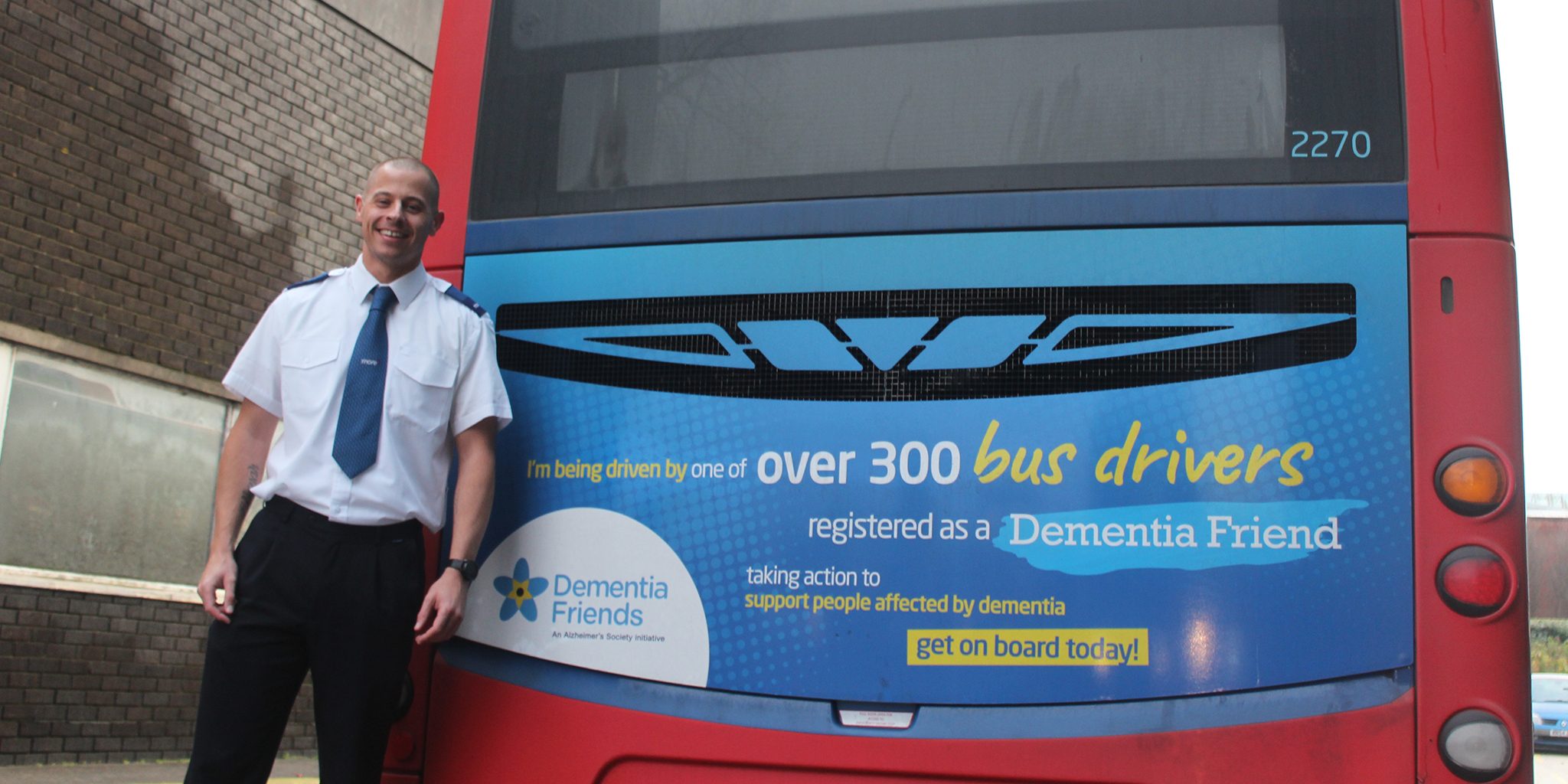Photo of a morebus driver standing next to a bus promoting dementia friendly bus drivers
