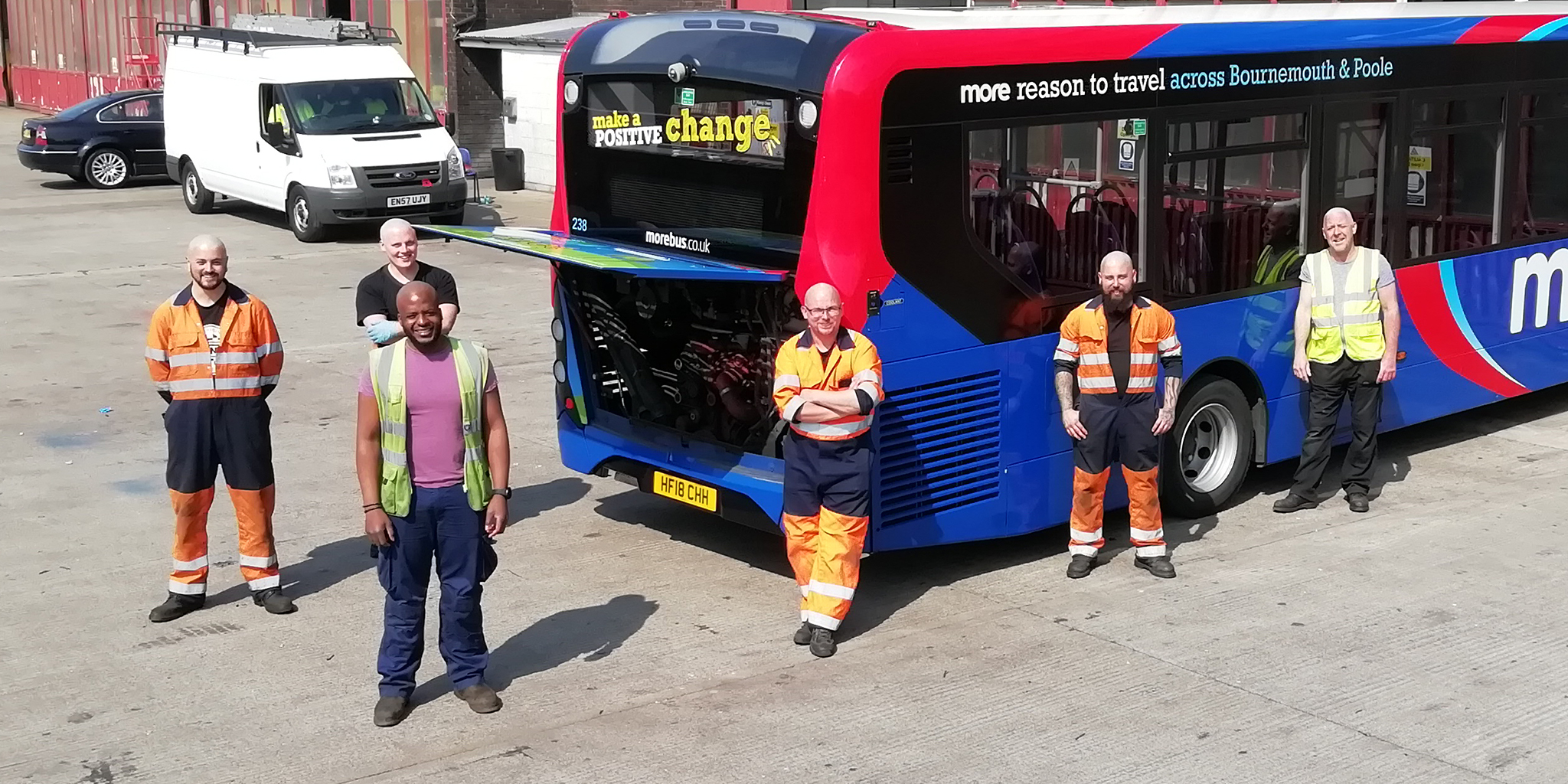 Photo of morebus engineers with shaved heads next to a morebus bus