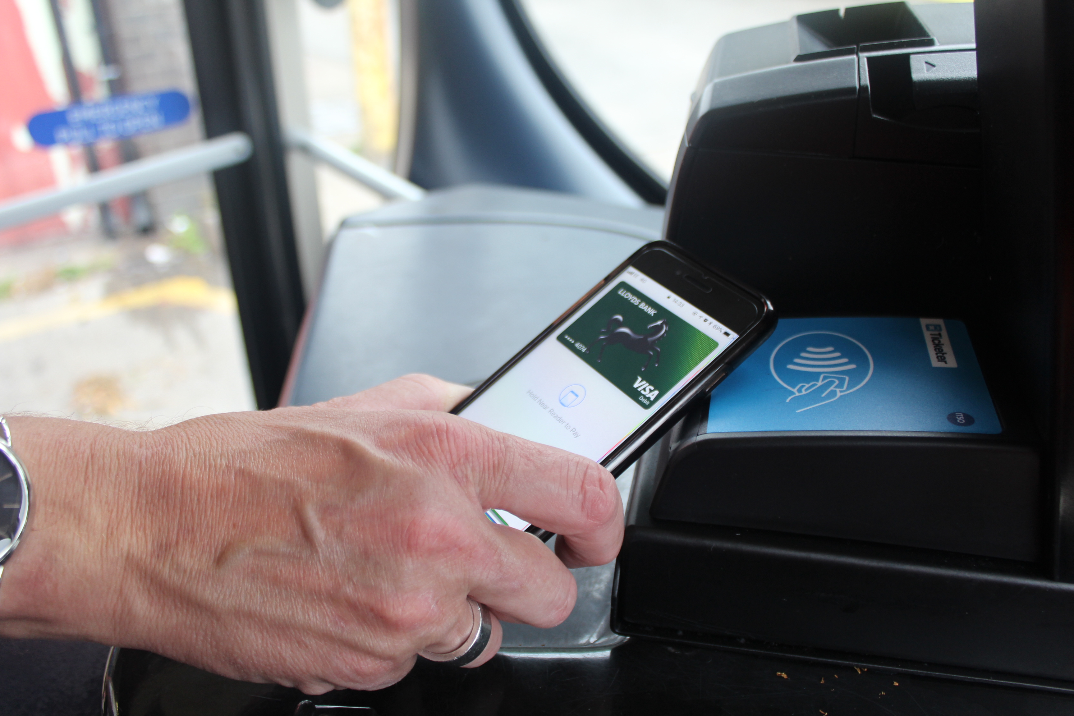 Photo of customer paying with contactless on-board a more bus