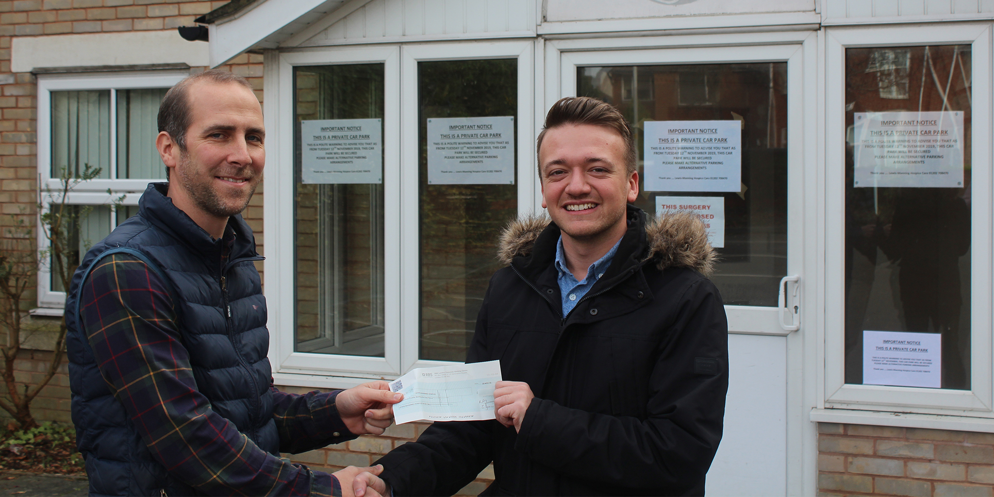 Photo of Tom Goodinge from Lewis-Manning Hospice receiving a cheque from morebus's Joe Quinlan
