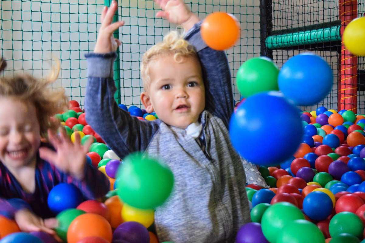 A little boy plays in the mulitcoloured ball pit.
