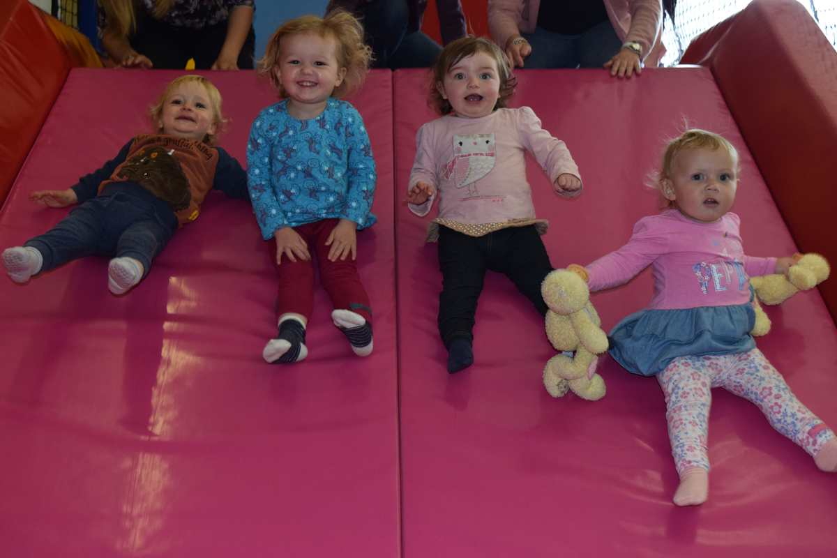 4 children slide down a pink slide in the childrens play area.