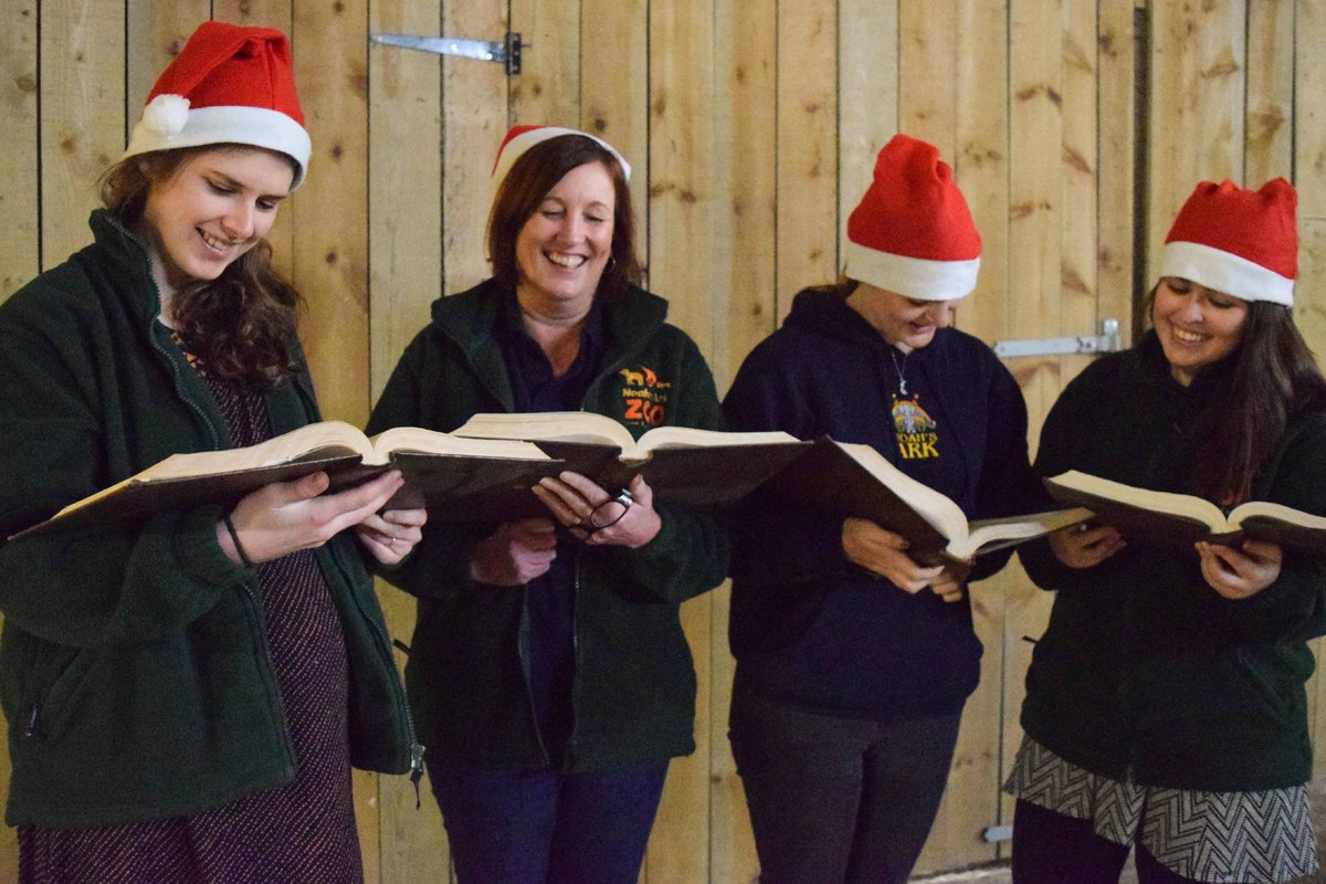 Zoo Keepers singing carols wearing red christmas hats