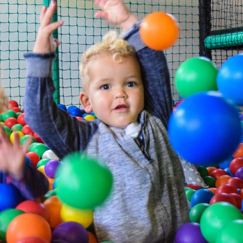 young boy plays in the ball pit
