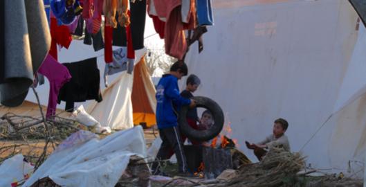 Nens refugiats fent una foguera al camp oficial de Kherso.