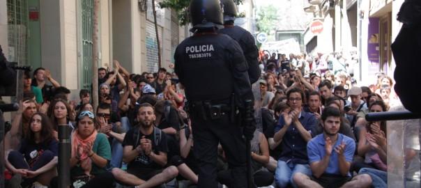 Els manifestants pel 'Banc Expropiat' de Gràcia asseguts davant del cordó policial. 29 de maig de 2016. (Horitzontal)