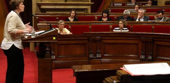 La portaveu de la comissió promotora de la ILP d'Educació, Rosa Cañadell, i la consellera d'Ensenyament, Meritxell Ruiz, escolten la intervenció de la diputada de JxSí Anna Simó
