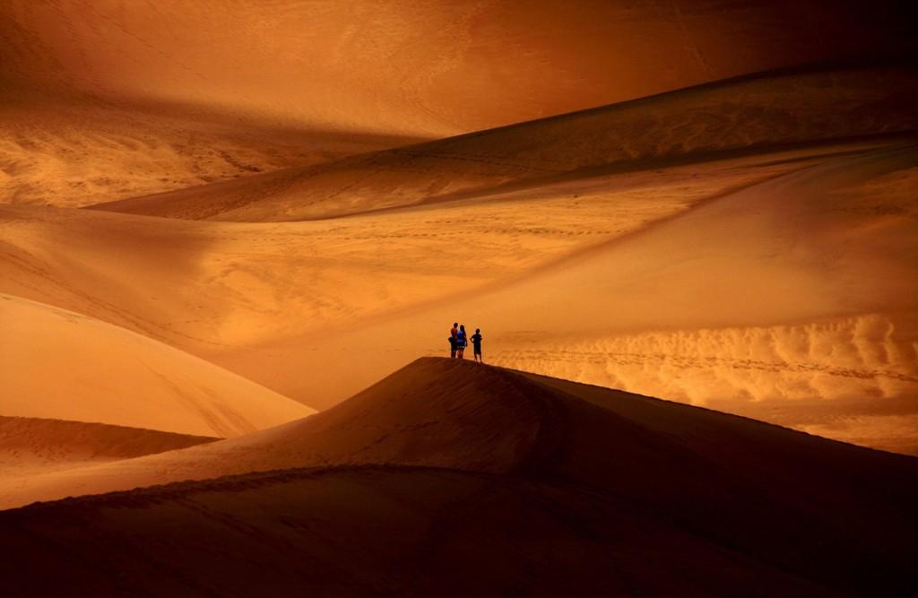Un grup de persones entre les dunes d'un desert de Colorado, Estats Units (fotografia: Viral Padiya)