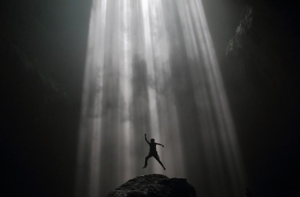 Un home salta dins la cova de Jomblang, Indonèsia (fotografia: Tomy Tomy)