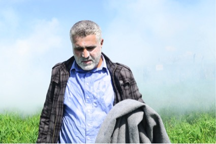 Un refugiat davant d'un núvol de gas lacrimogen