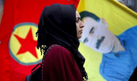 Una dona camina davant una bandera amb la cara d'Abdullah Öcalan.