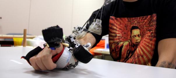 En Sergio, un pacient de l'Institut Guttmann, mostra la ma robòtica desenvolupada per investigadors alemanys i italians.