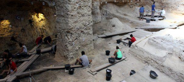Pla obert del jaciment de l'Abric Romaní amb diverses persones treballant en la campanya d'excavacions. 10 d'agost de 2016. (Horitzontal)