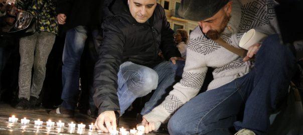 Dos homes encenent espelmes a la plaça del Mercadal de Reus