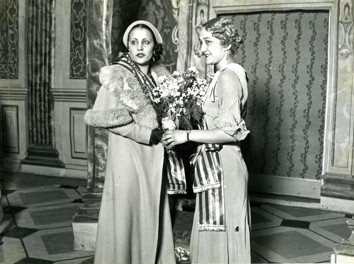 """Elecció de Miss Catalunya 1934. Foto de Carlos Pérez de Rozas. Concurs organitzat per """"Dia Gráfico i LaNoche"""". Celia Zobal, Miss Mecanògrafa 1933, lliura la banda a EloisaGonzález, escollida Miss Mecanògrafa 1934. Acte celebrat al TeatreNovedades. D'esquerra a dreta, Miss Mecanògrafa 1934 i Miss Mecanògrafa1933"""