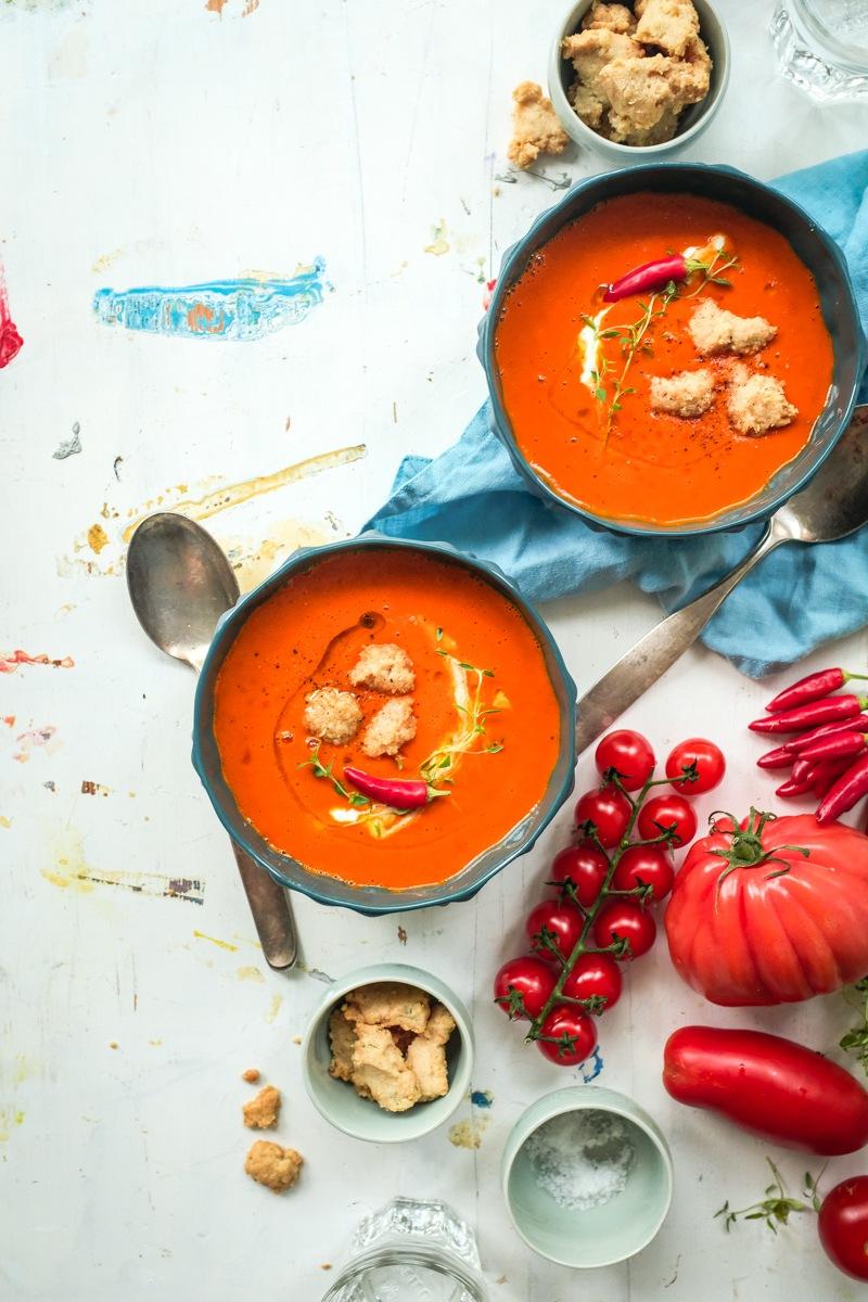 Rezept aromatische sommersuppe mit ofengerösteten tomaten und herzhaften crumbles aus manchegokäse, pinienkernen und thymian