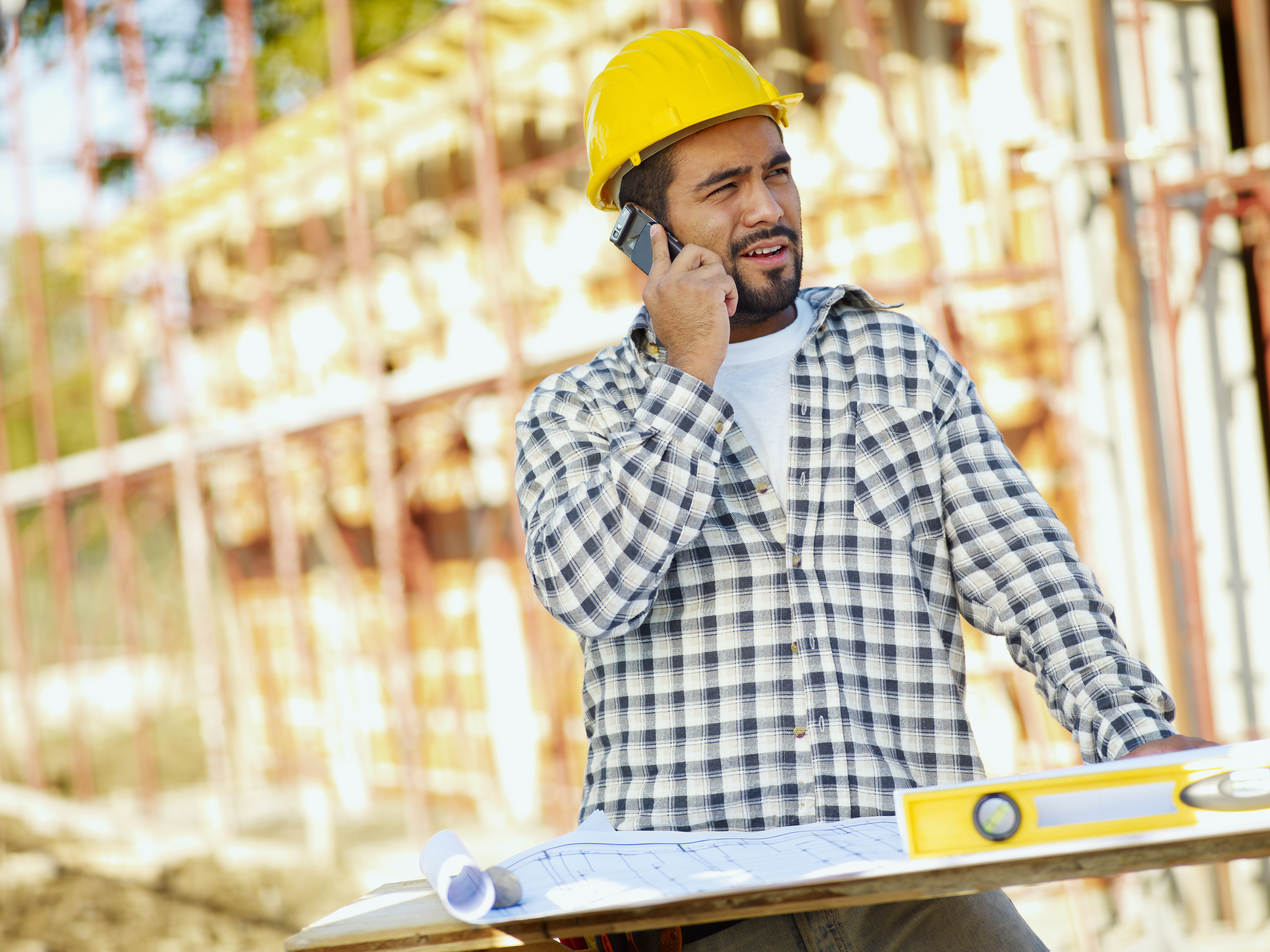 construction worker talking on the phone to his boss