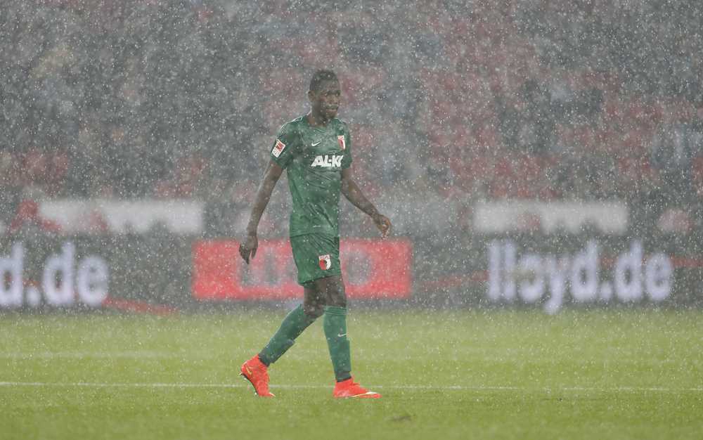 Augsburg's Baba leaves the pitch due to heavy rain during his team's Bundesliga German first league soccer match against Bayer Leverkusen in Leverkusen